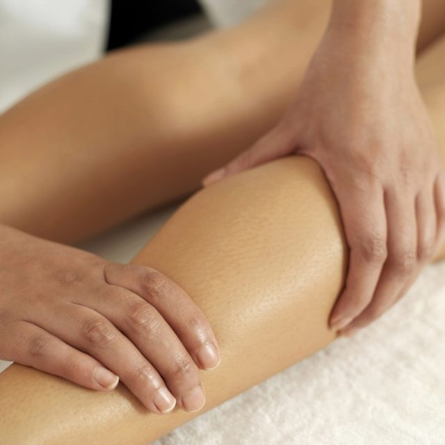 therapist prforming sports massage on patient's leg