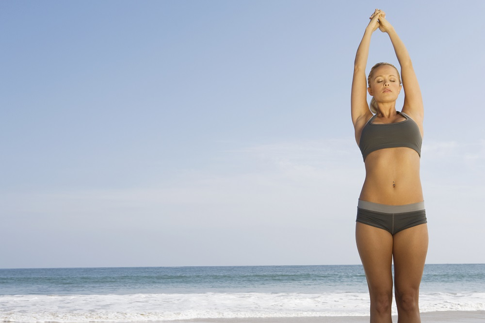woman doing back strengthening exercises on a beach